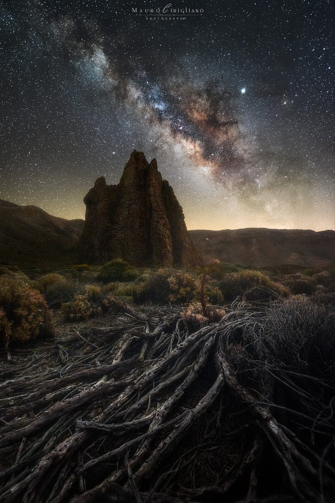 rock under starry sky with dry grass in the ground in tenerife