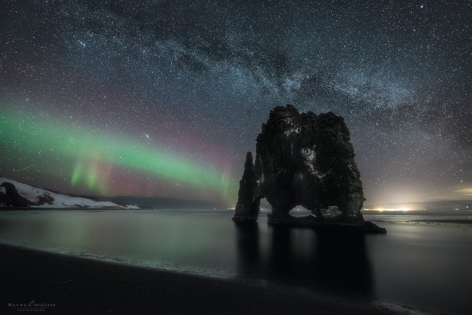 black rock into the sea under northern lights