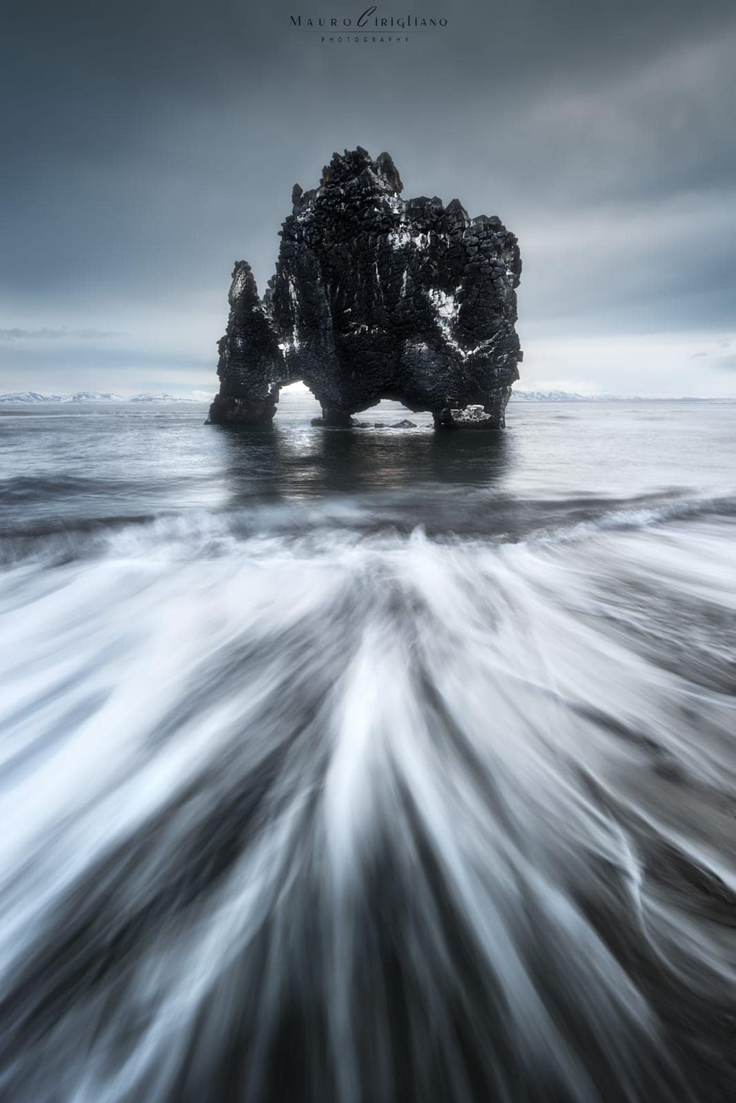 Roccia nera nel mare con cielo nuvoloso
