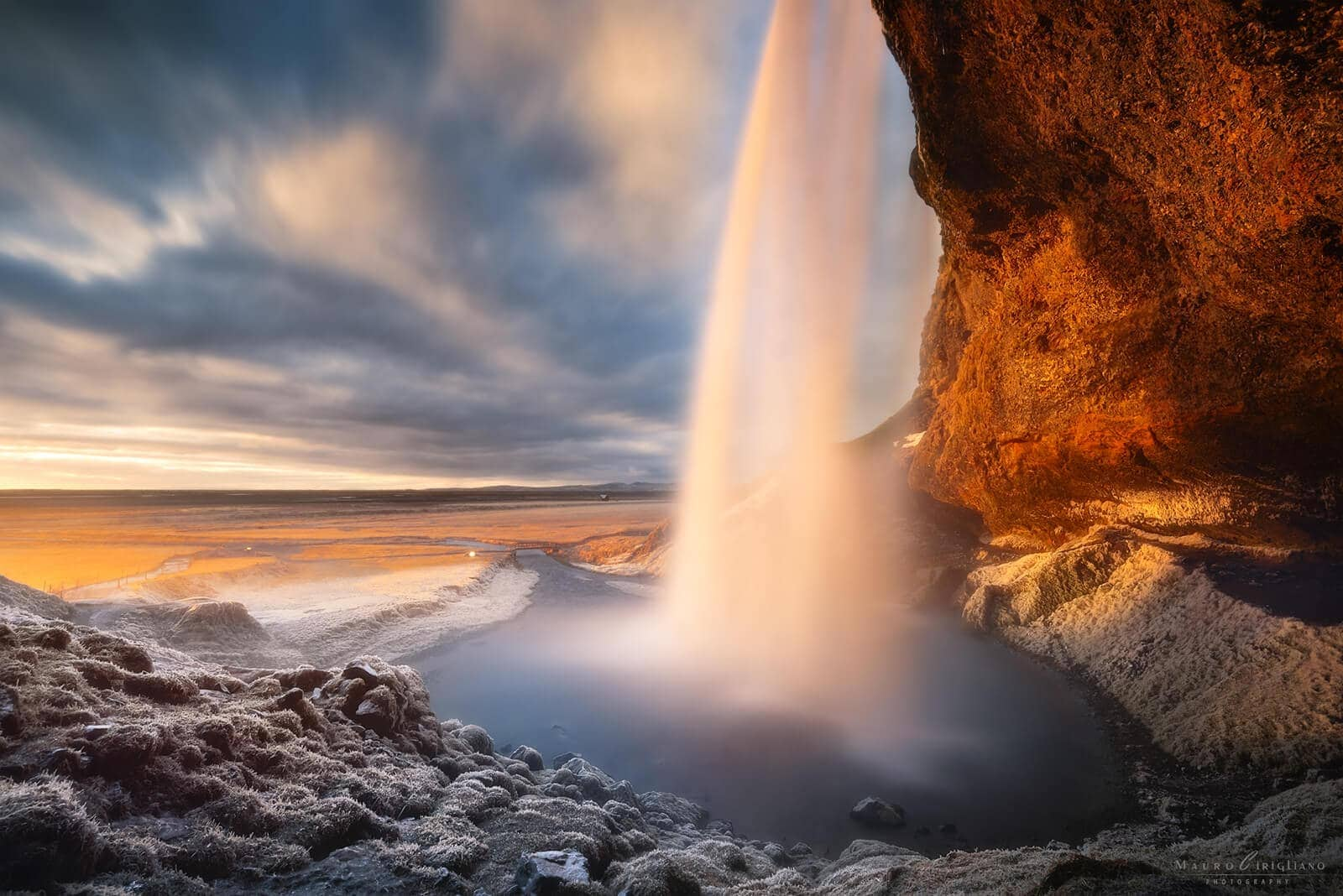 Cascata islandese irradiata dal sole al tramonto