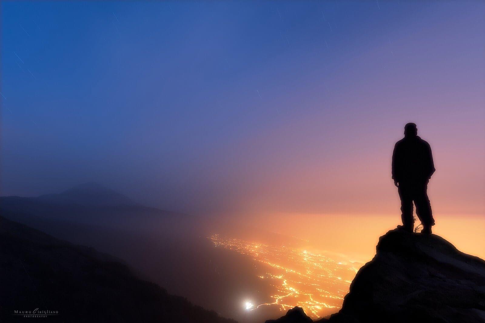 persona che osserva di notte luci città