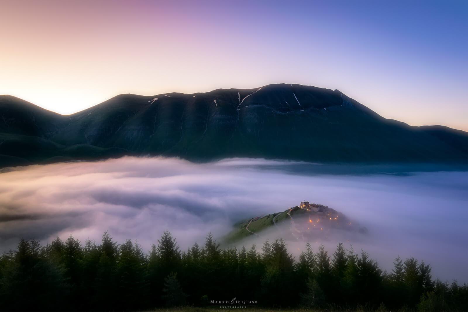 vallata colma di nebbia che circonda paesino
