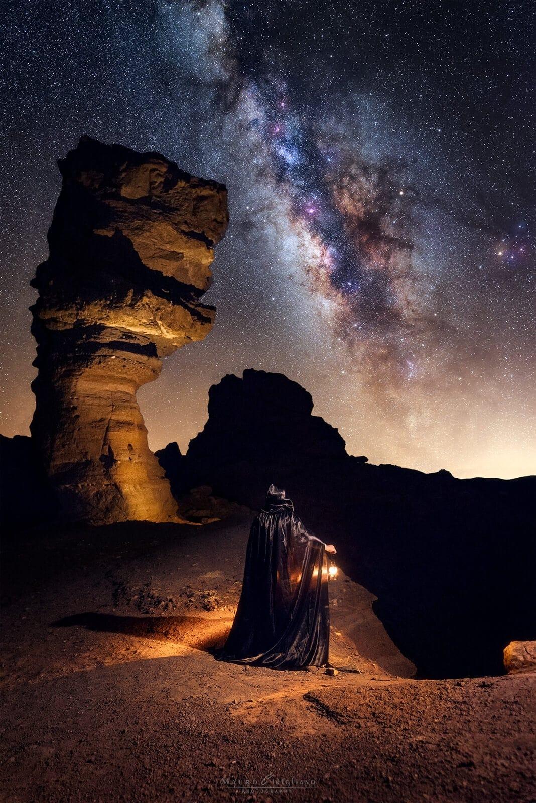 persona con mantello e lanterna che illumina roccia cinchado a tenerife sotto cielo stellato