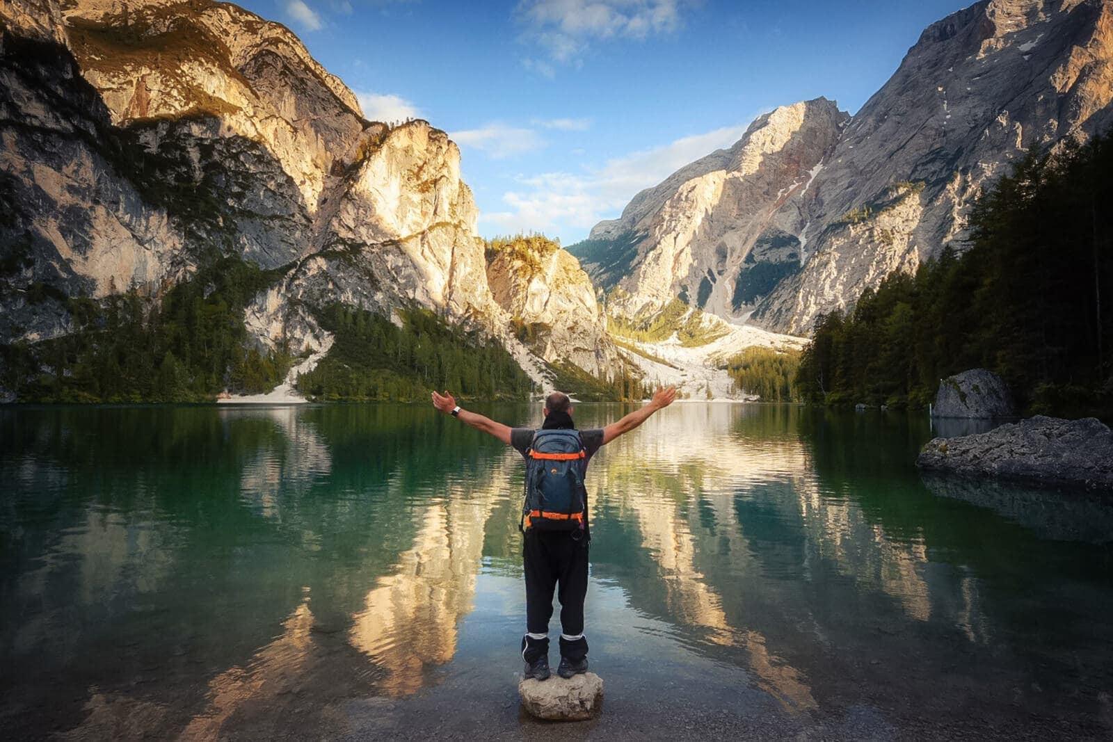 lago di braies con montagne sullo sfondo e persona a braccia alzate in primo piano