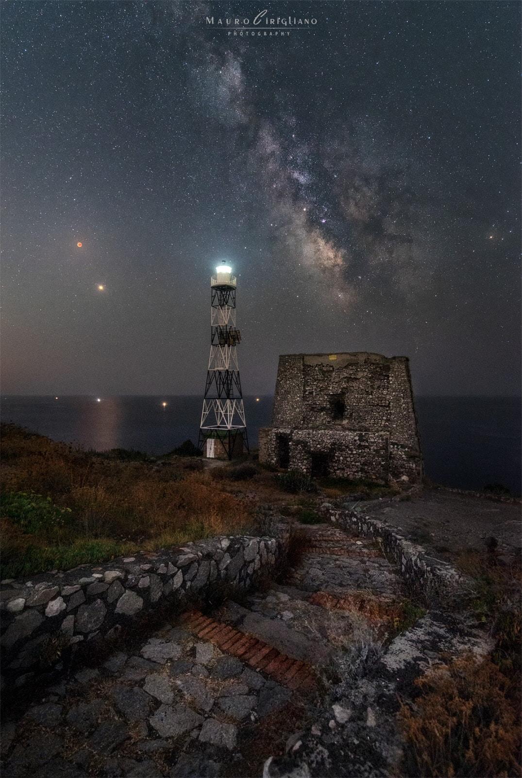 eclissi lunare totale e via lattea su antica torre saracena