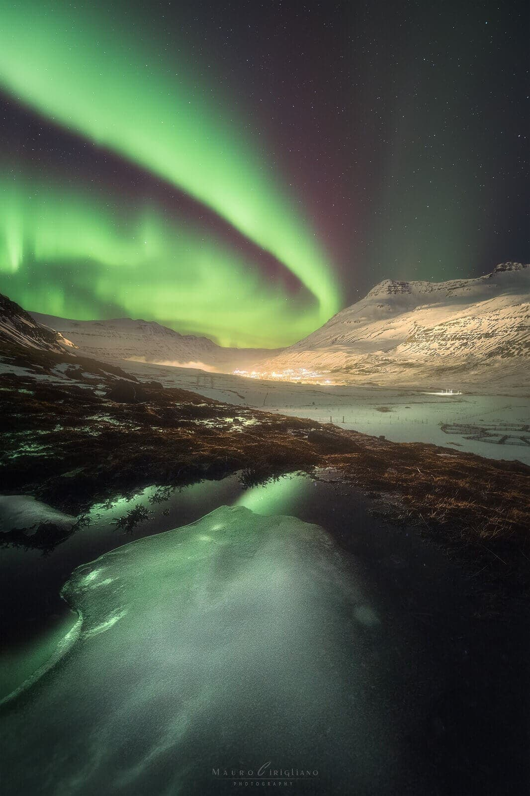 luci di un paesino con aurora boreale