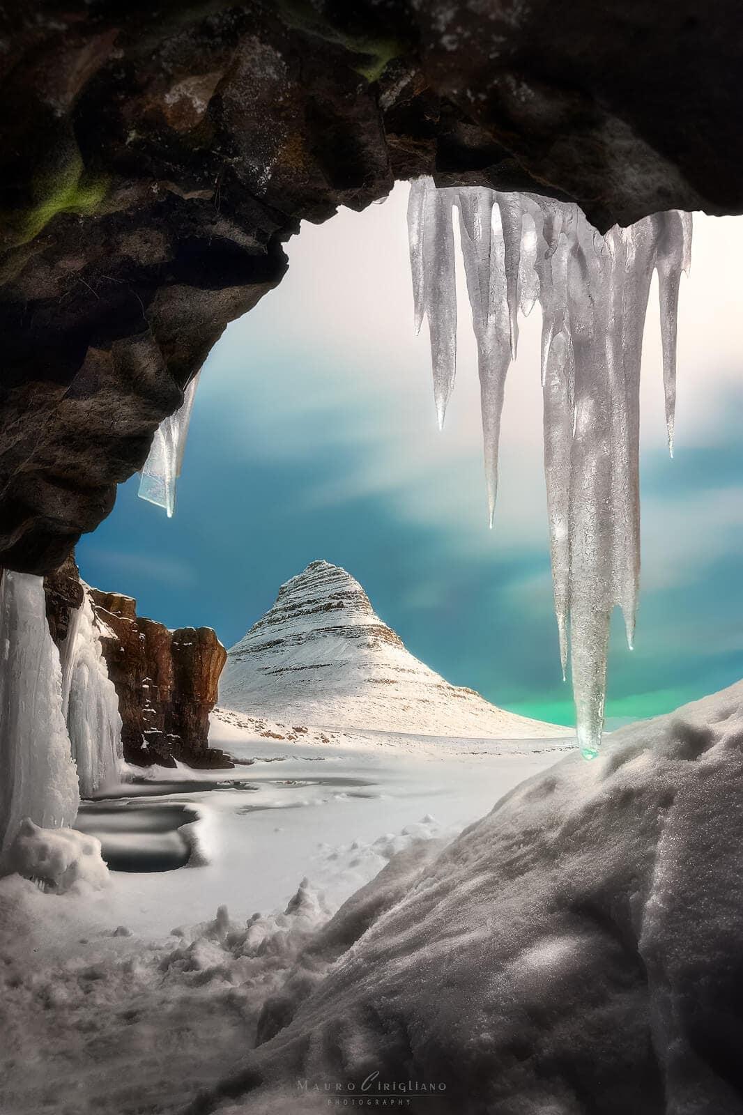 monte imbiancato da neve osservato da grotta con ghiaccio