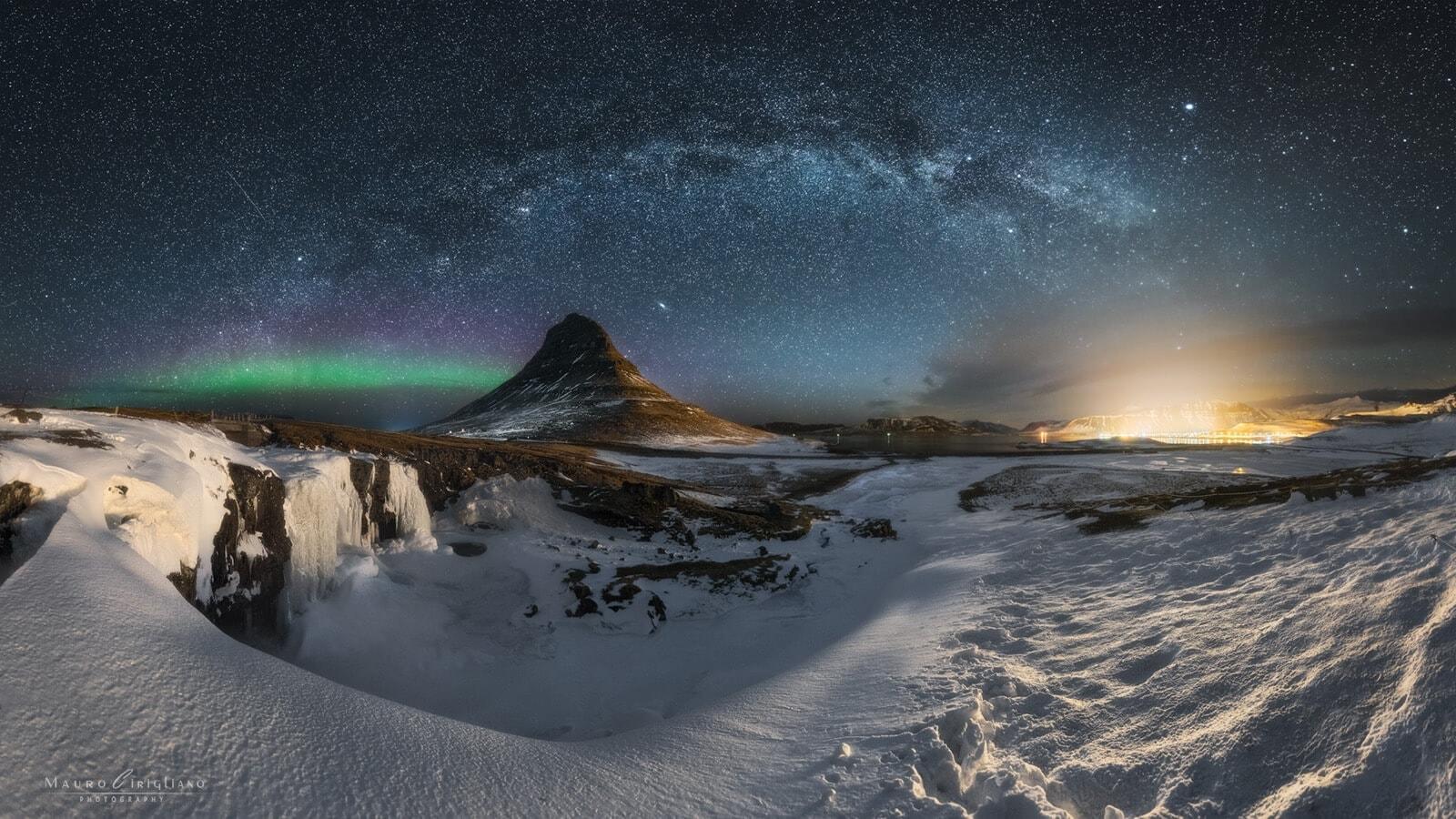 Monte kirkjufell con arco via lattea e aurora boreale