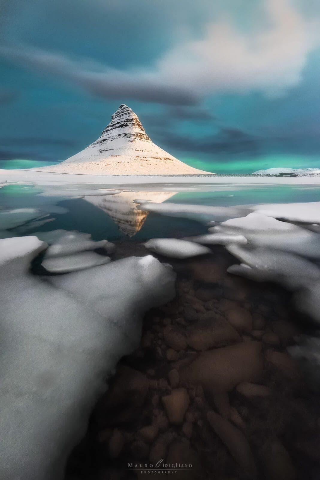 lago con ghiaccio e neve e monte in punta innevato in islanda