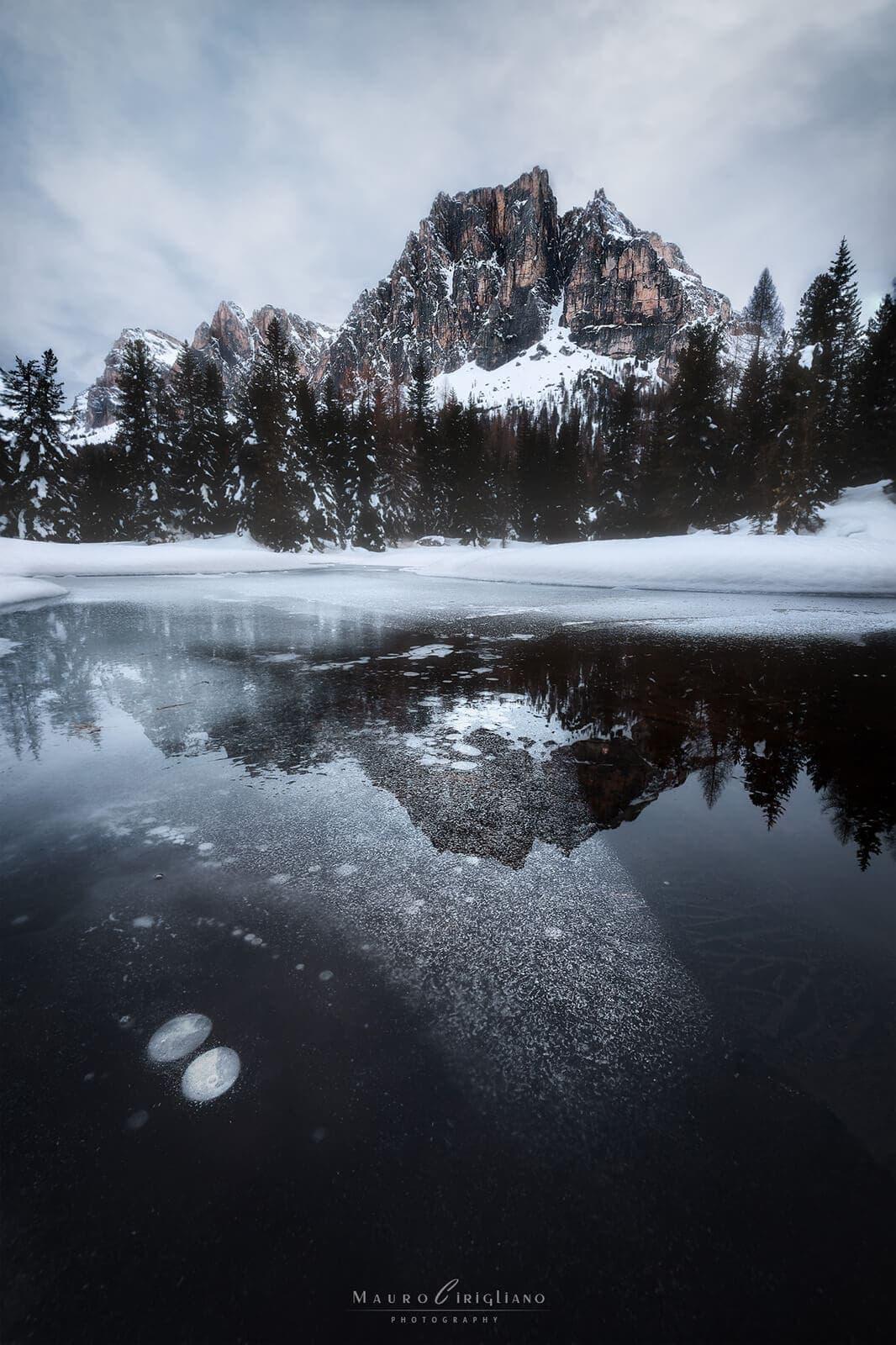 monte tofana riflesso in acque ghiacciate in un giorno nuvoloso