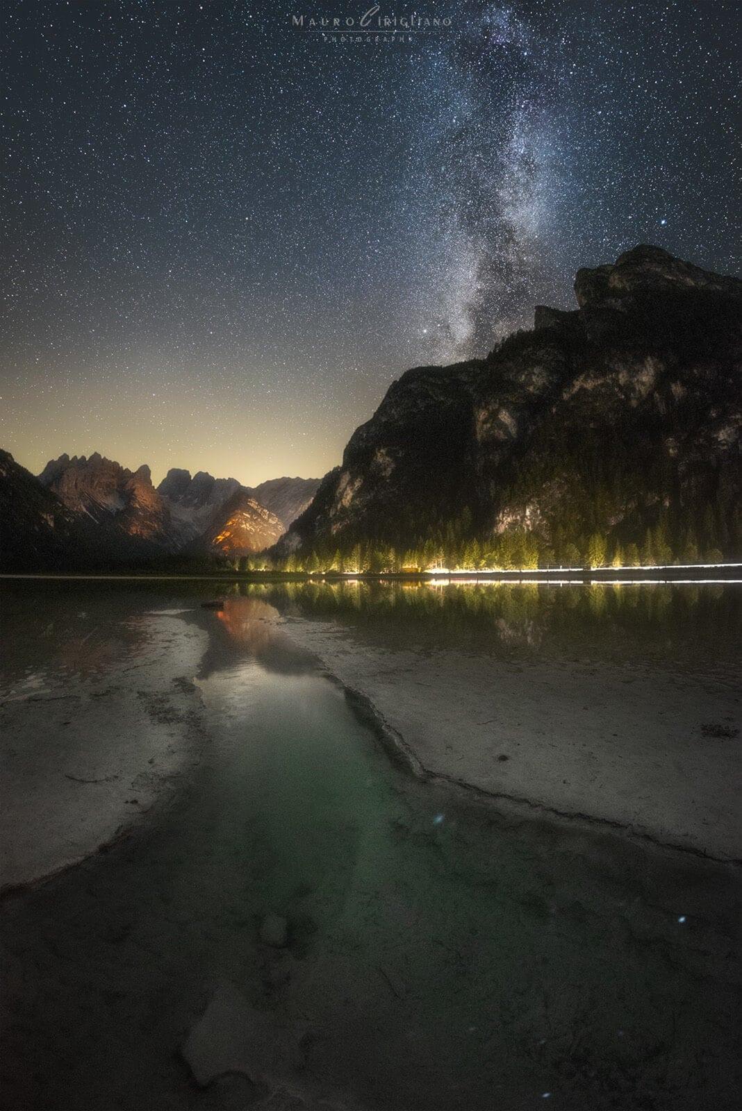 riva del lago landro con montagna e stelle sullo sfondo