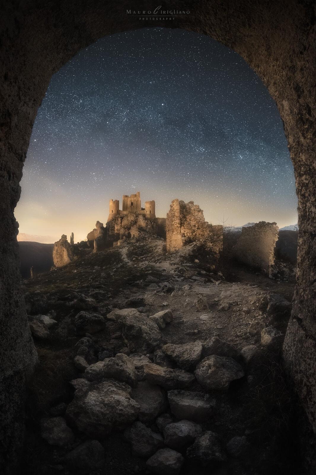 via lattea sopra castello incorniciato da arco di pietra
