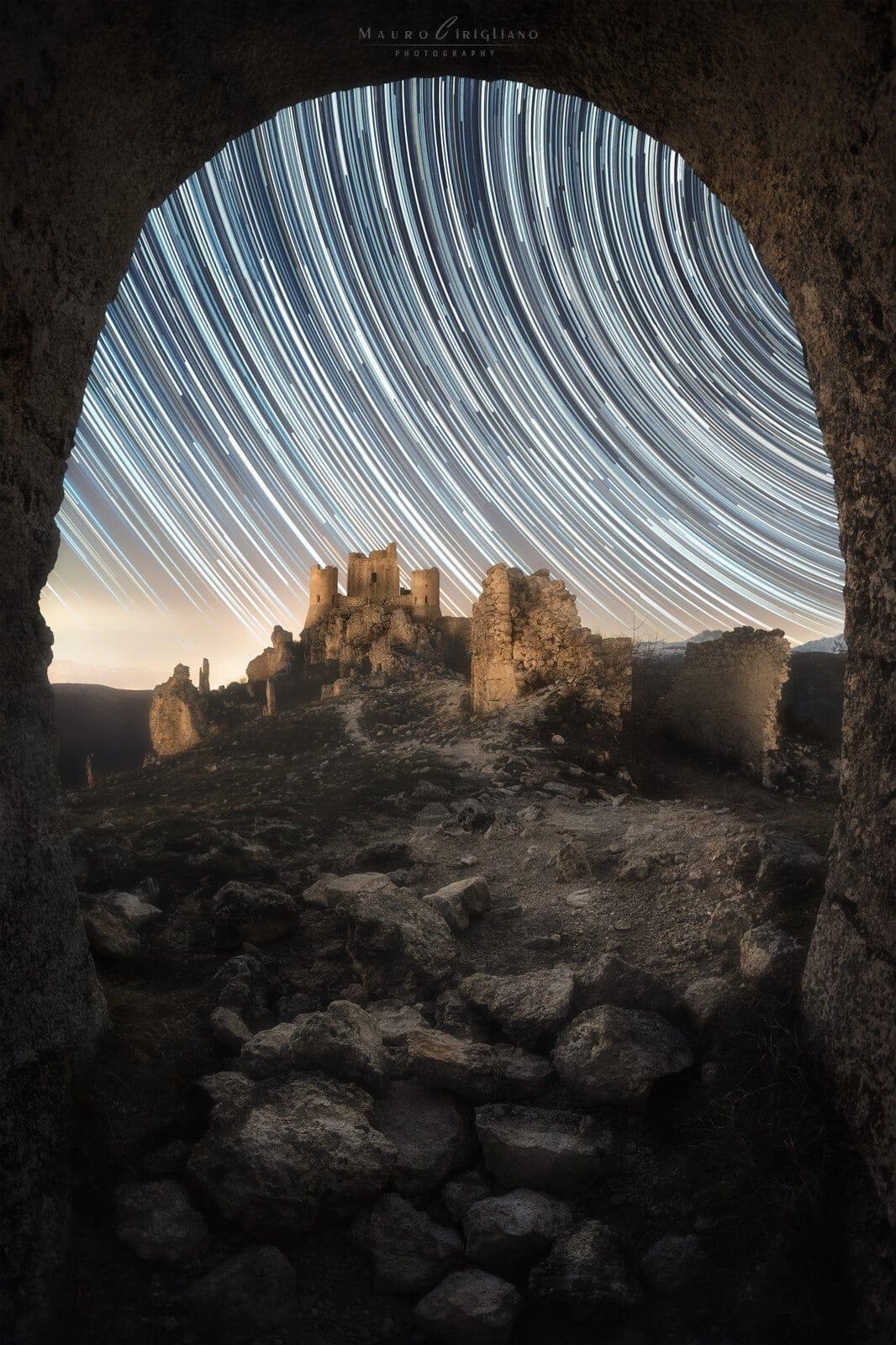 startrail con castello visto da arco di pietra