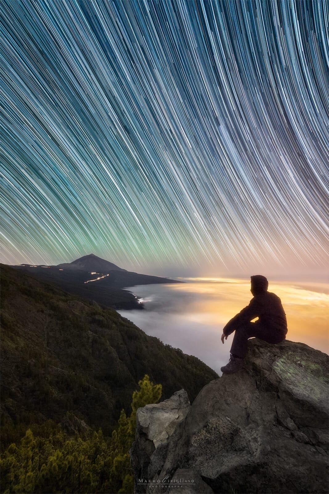 persona seduta di notte davanti a panorama coperto da nuvole