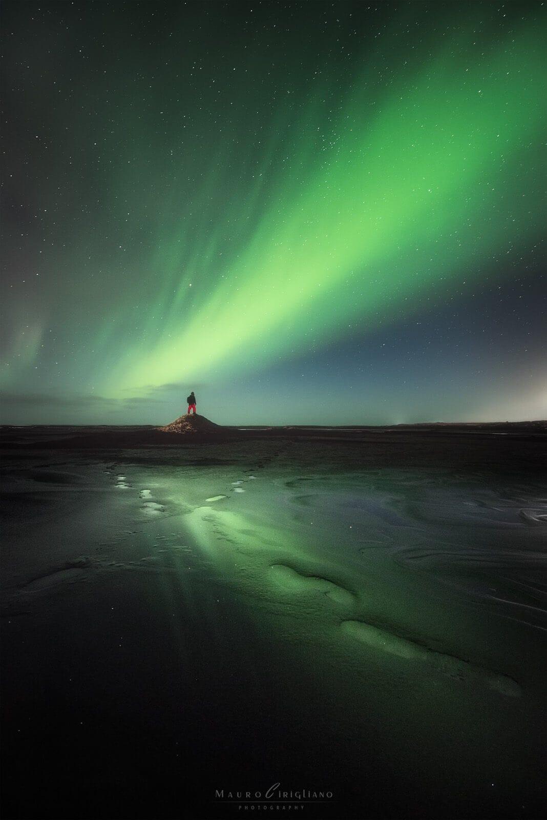 sagoma umana su duna che osserva aurora boreale in islanda