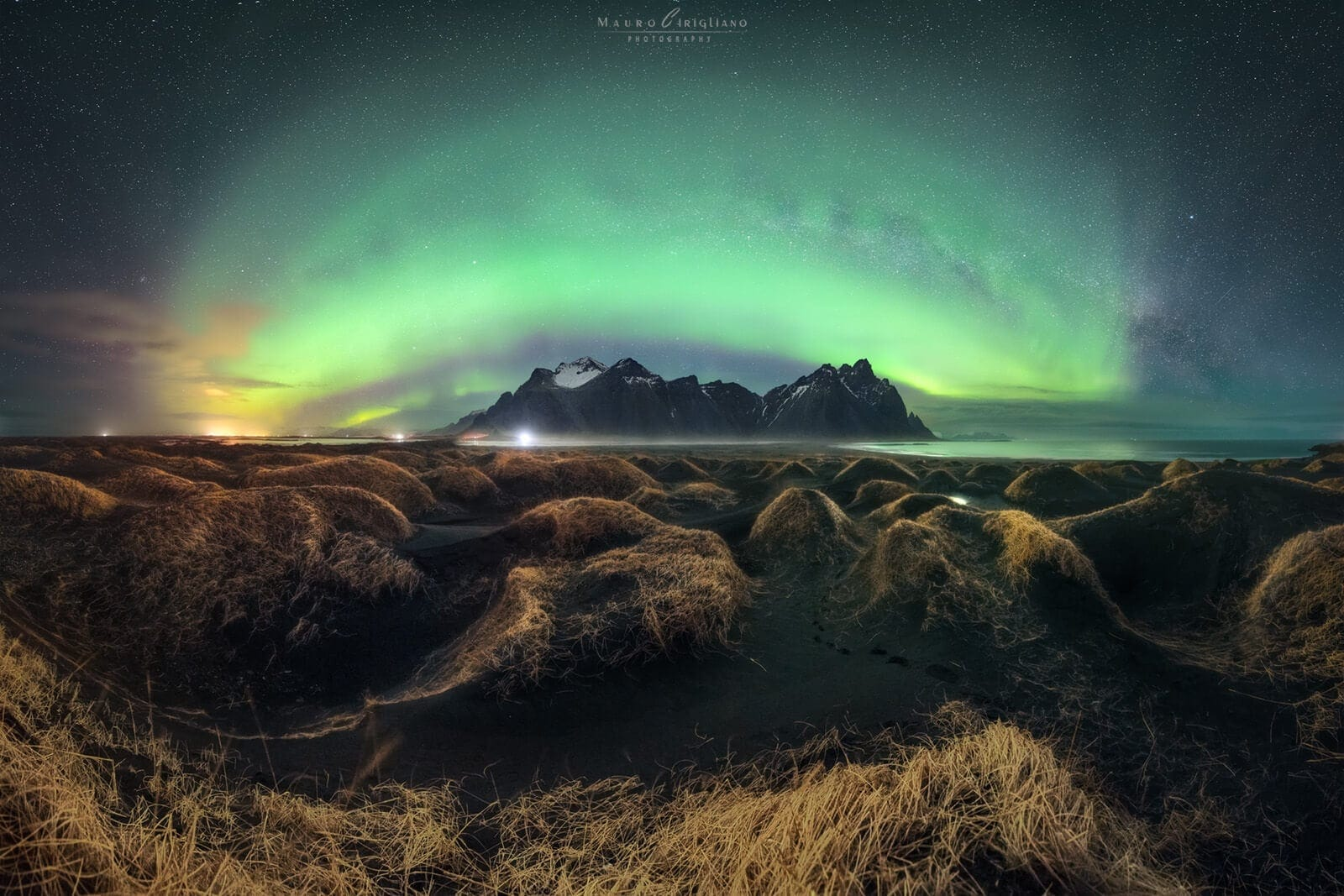 Monte con arco aurora boreale e dune di sabbia con erba gialla in primo piano